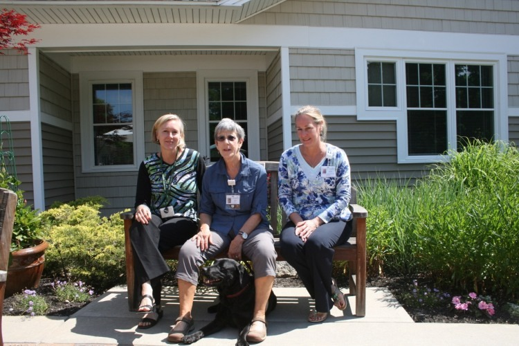 Therapy dog Sophie on the terrace outside Gosnell Memorial Hospice House with (from left) Stefanie Fairchild, Hospice of Southern Maine Volunteer Coordinator; Nan Butterfield, PawPrints volunteer and Sophie's handler; and Kelli Pattie, Hospice Southern Maine Director of Volunteer Services.