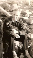 E. B. White sitting on the beach with his dog Minnie.